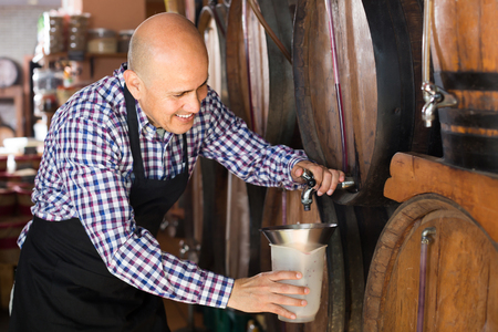 Elderly man wine maker taking wine from wood in winery Stock Photo
