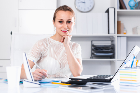 Portrait of young smiling american girl in the office sitting at the table