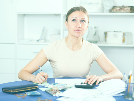 paying: Upset woman calculating domestic finances with calculator and bills on table