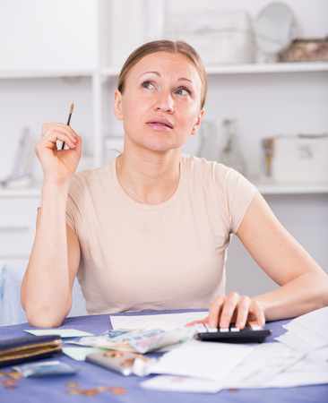 Upset woman calculating domestic finances with calculator and bills on table