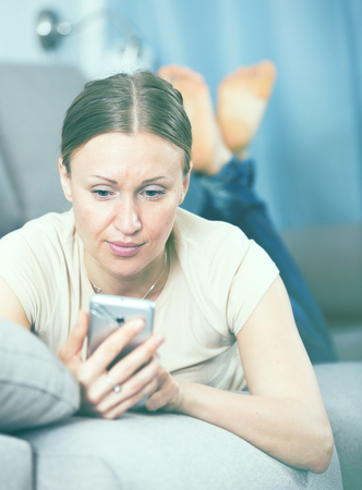 Upset woman resting on sofa and reading text message on phone