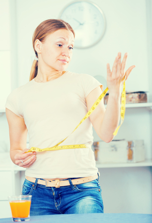 Woman measuring waistline with yellow tape frustrated by increasing in volume