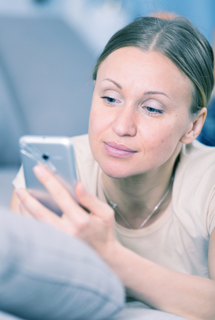 disagreeing: Worried young woman looking at her smartphone on sofa at home