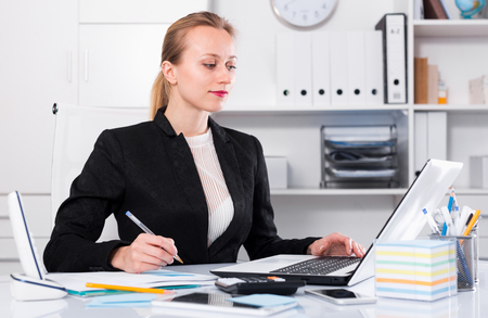 positiv: Cheerful woman working in the office at the laptop