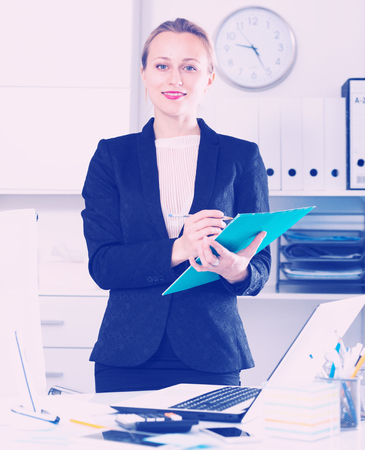 Portrait of cheerful female in the office standing with folder