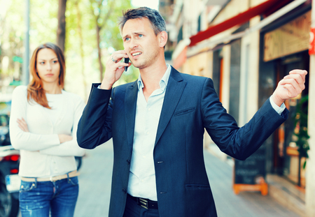 vexation: Young man during serious telephone conversation on background of disappointed girl