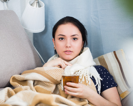 Young woman catching cold, wrapping in blanket and drinking hot tea Reklamní fotografie