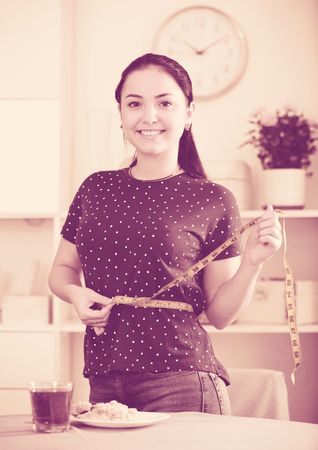 Smiling young woman measuring waist with tape near table with breakfast