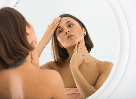 Young woman checking her face in mirror in morning