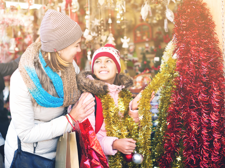 overspending: Smiling little girl with young mom buying decorations for Xmas. Focus on girl