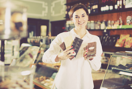 sorts: Young female client choosing delicious bar of chocolate in confectionery