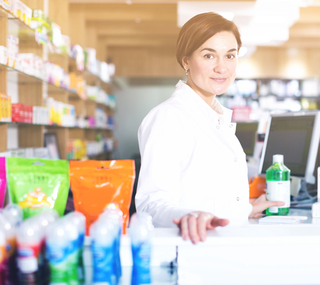Glad woman pharmacist ready to assist in choosing at counter in pharmacy
