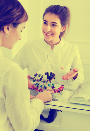 schemes: Smiling satisfied  female manicurist showing lacquer color schemes in nail salon Stock Photo