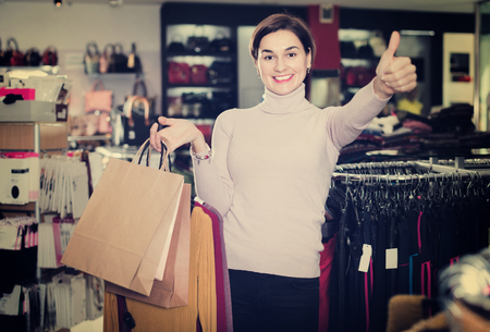 acquiring: Smiling happy positive female shopper boasting her purchases in women's cloths shop