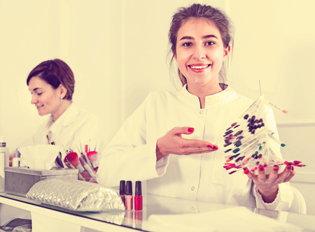 schemes: Satisfied pleasant cheerful female manicurist showing lacquer color schemes in nail salon Stock Photo