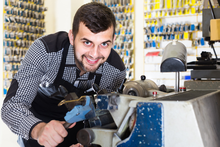 specialized job: Smiling european male worker shaping new key in repair workshop