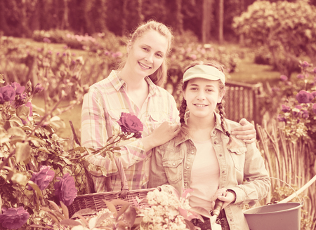 smiling blond  woman and teen holding a basket and standing in the park of roses. Stock Photo
