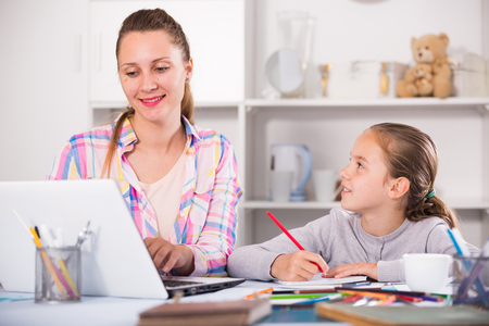 Portrait of cheerful woman and smiling girl writting  with pen