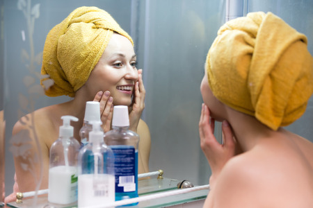 grooming product: Cheerful woman with towel on head after shower looking at her face at mirror in bathroom