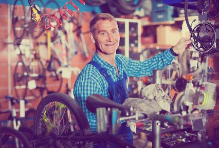 friendly smiling man seller wearing uniform fixing bike wheel in store Stock Photo