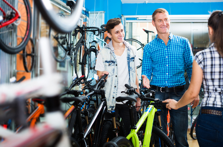 Father with happy young teenager boy asking positive female seller for help in sport bike shop