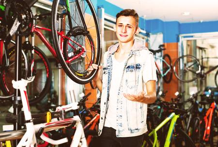 cheerful  boy teenager choosing new bicycle in sport hypermarket