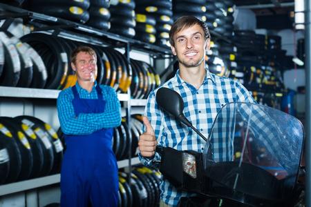Happy man customer holding his motorcycle at maintenance point