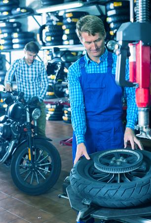 portrait of professional mature male mechanic in uniform working with bike wheel in workshop