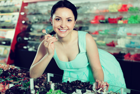 Happy young woman buying candy at gifts shop