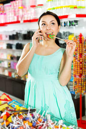 Happy girl in the store picks up candy and speaks by mobile