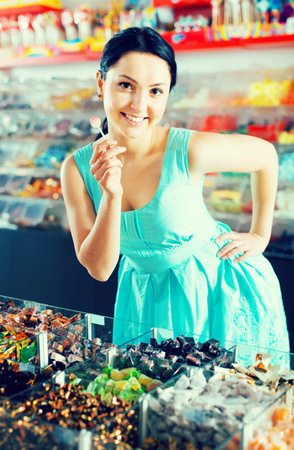 pleased sexy female posing in the store with lolly on the background of counters with sweets Stock Photo