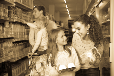 Happy young family with two daughters purchasing yoghurts in supermarket