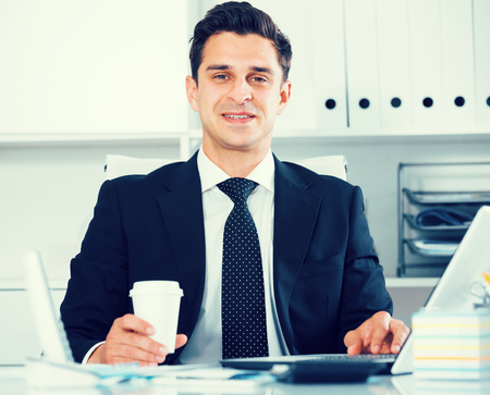 Successful businessman using laptop at workplace