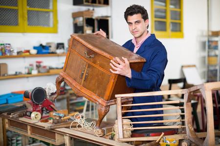 Portrait of an expert in restoration of antique furniture in workroom Imagens
