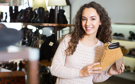Smiling brunette girl choosing fashion winter shoes in a shoe store