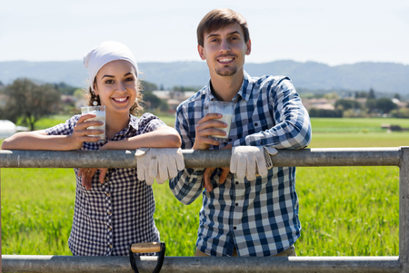 smiling young russian man and woman chatting and enjoying milk outdoors Stock Photo