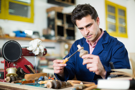 Skilled concentrated joiner working in workshop with chisel in hands Stock Photo