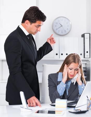 Uomo d'affari arrabbiato con il collega femminile sul posto di lavoro in ufficio