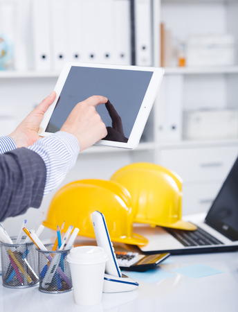 Woman using touchscreen tablet on background with blured office interior