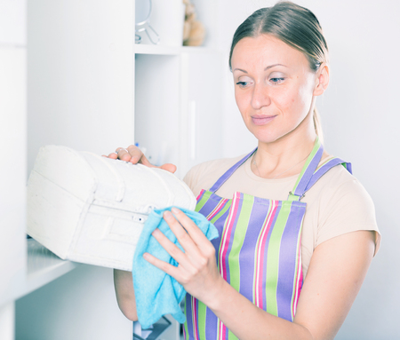 narrowly: Woman in striped apron wiping dust on jewelry box at home