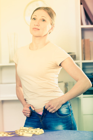 Upset woman with measuring tape on table trying to zip up jeans