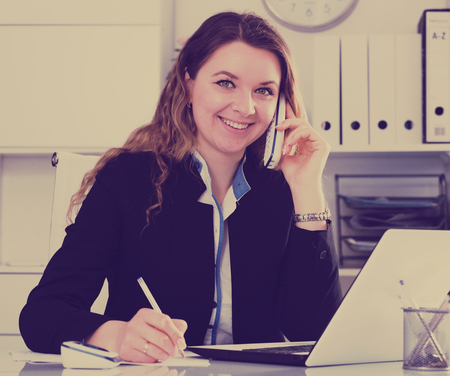Cheerful bussineswoman filling up documents and talking on the phone Banco de Imagens