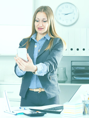 Successful business woman using phone at workplace in office