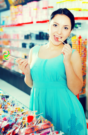 Beautiful young woman posing to photographer with lollypop at candies shop Stock Photo