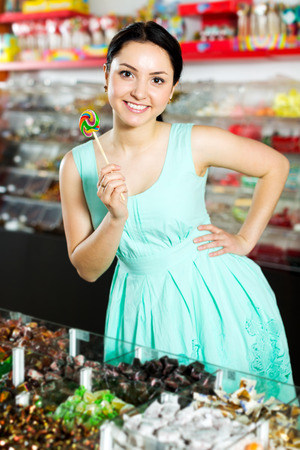 Portrait adult girl posing to photographer with lollypop at candies shop Stock Photo