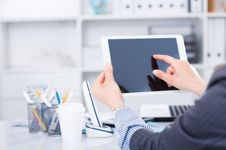 Business woman holding and using tablet at workplace in office Stock Photo