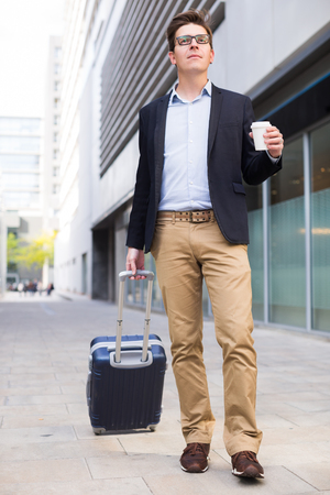 Portrait of cheerful male standing with bag at the modern street Stock Photo
