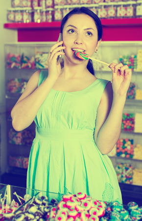 Smiling female speaking by mobile and picking candy in hands