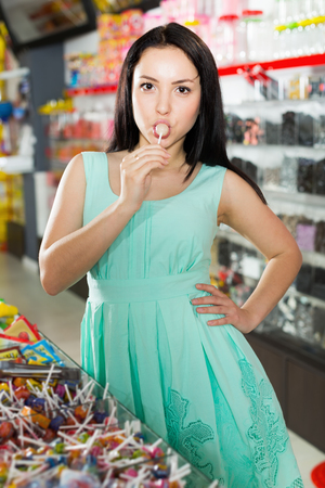 Portrait of sexy young woman suck lollipop at candy store