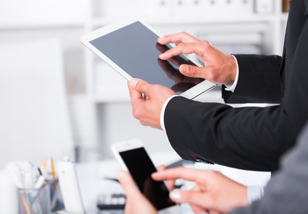 Hands of two business partners using devices in design office Stock Photo